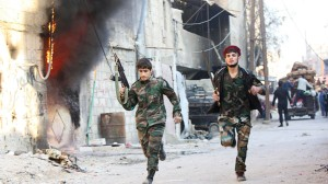 Shi'ite fighters, fighting along forces loyal to Syria's President Bashar al-Assad, run with their weapons along a deserted street in Hujaira town, south of Damascus